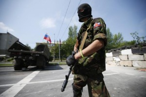 A member of a newly-formed pro-Russian armed group called the Russian Orthodox Army mans a barricade near Donetsk airport
